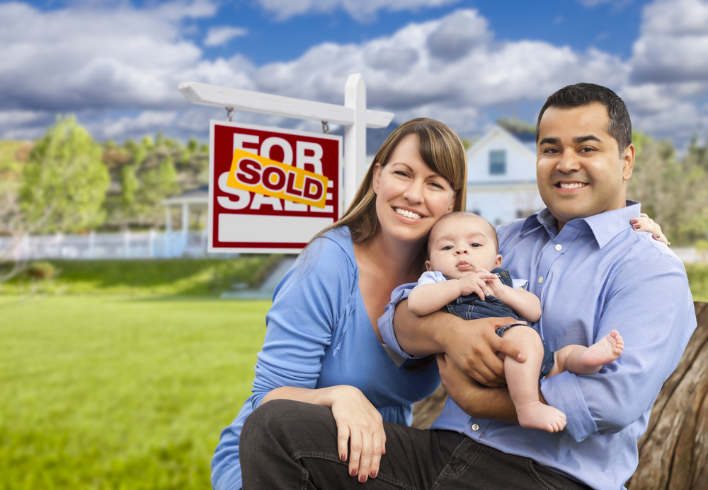 Happy Mixed Race Young Family in Front of Sold Home For Sale Real Estate Sign and House - Rapid Mortgage Company